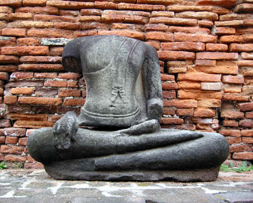 A headless Buddha statue pays tribute to the past, Ayutthaya, Thailand