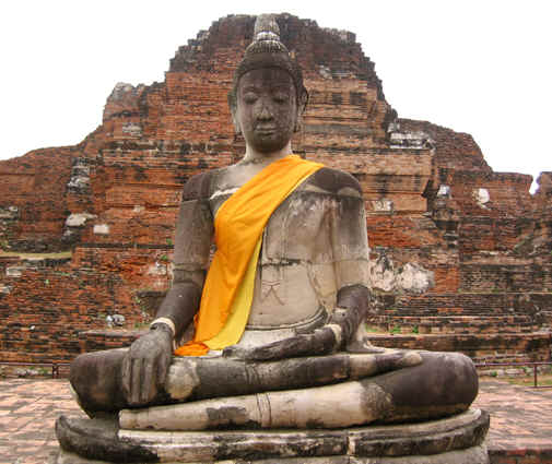 This statue remains whole, draped in orange/gold cloth by devotees, Ayutthaya, Thailand