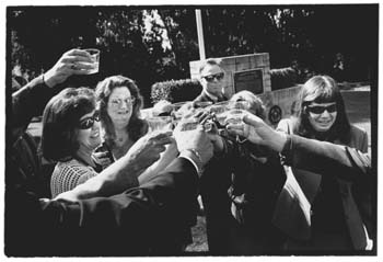 Close family and friends at the gravesite, toasting with champagne