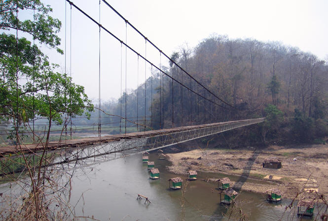 Rickety bridge over river with small village structures below, Hilltribe village, Thailand