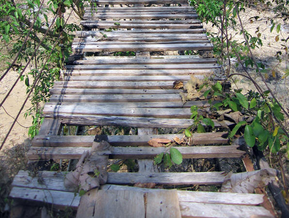 A closer look at the missing and spongy planks of the bridge Hillside village, Thailand
