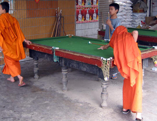 MONKS PLAYING POOL IN REMOTE VILLAGE