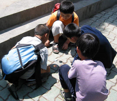 BOYS PLAYING GAME ON SIDEWALK