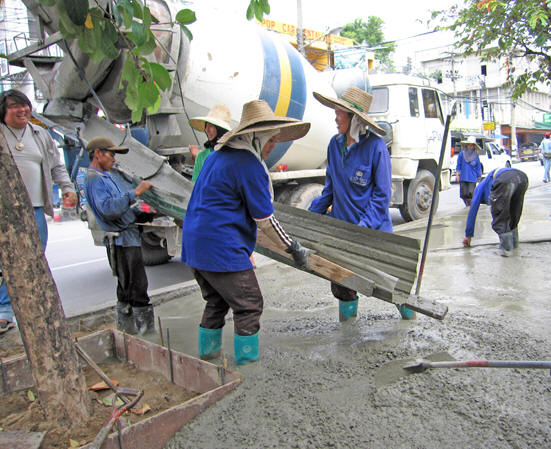 Women ankle deep in freshly poured concrete manage the fresh pour. Chiang Mai, Thailand