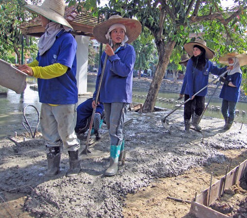 Thai women in rubber boots standing on wet concrete, waiting for the next pour. Chiang Mai, Thailand
