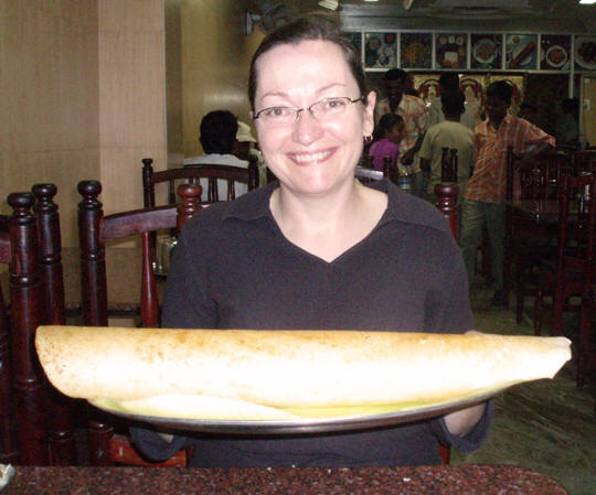 Erin holds a HUGE South Indian Dosai (crepe). Let's eat!