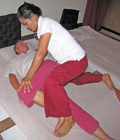 May doing a spinal twist on Billy. Chiang Mai massage, Thailand