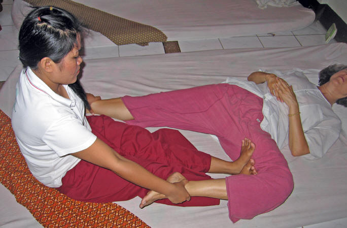 Stretching and pulling Akaisha's thighs. Chiang Mai, Thailand