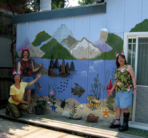 Three sisters with fuzzy devil horns stand in front of fantasy seaside village mural. Santa Cruz, California