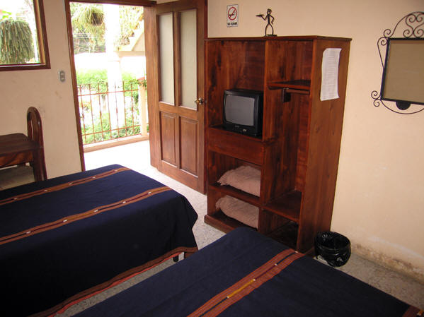 A typical room with firm beds, internet, hot water in a private bathroom, cable TV, a small desk and a balcony view.