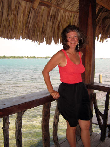 Akaisha leaning on a railing at a beach bar in Placencia, Belize
