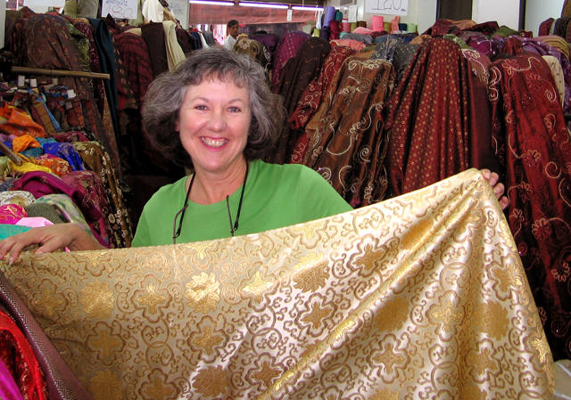 Akaisha surrounded by Chinese silk in fabric store in Chiang Mai, Thailand