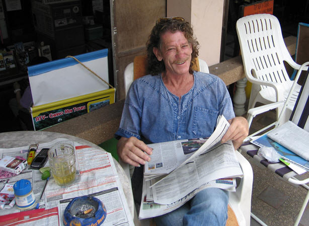 ROGER IN HIS POOLSIDE OFFICE CATCHING UP ON THE LATEST NEWS IN THAILAND