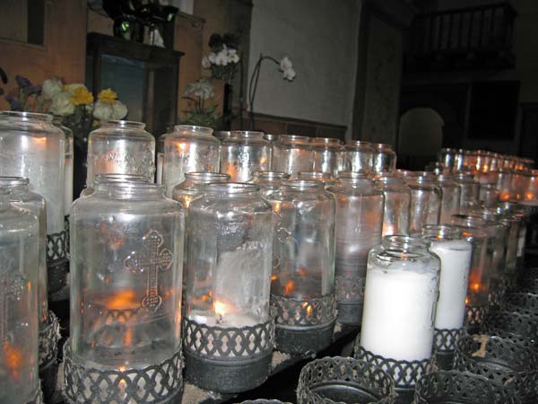 Votive candles to the sides of the altar