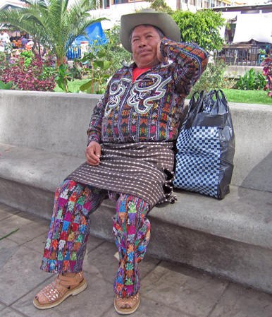 Wildly patterned and bright woven cloth make up this man's traditional shirt, pants and tzutes, the woven cloth about his hips.