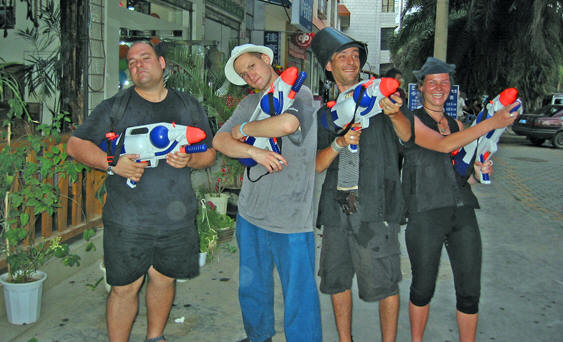 4 westerners posed and ready to go to battle with waterguns, Songkran festival, Jinghong, China