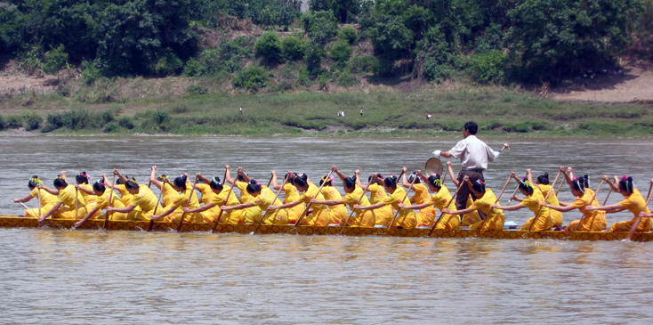 Chinese ladies in their Dragon Boat rowing in time with the gong, Jinghong China