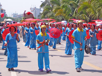 Women in blue dresses with bright red umbrellas in the Songkran Parade, Jinghong, China