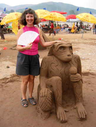 Akaisha with Chinese fan standing next to a large sand sculpture of a monkey