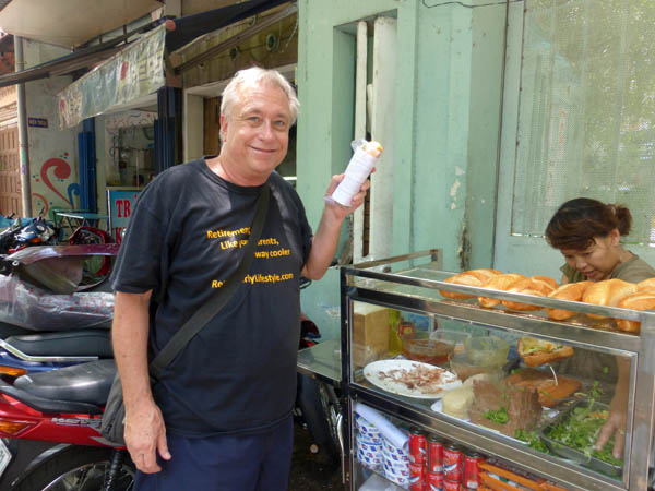 Billy buying a pate and pork sandwich in Saigon, Vietnam