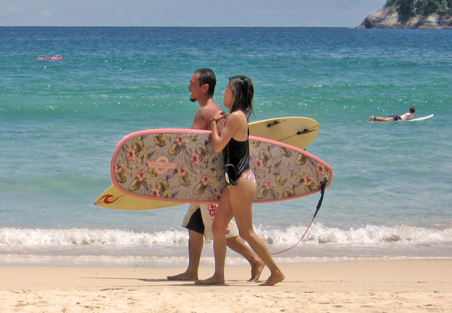 Female surfer with a floral patterned board, Kata Beach, Thailand