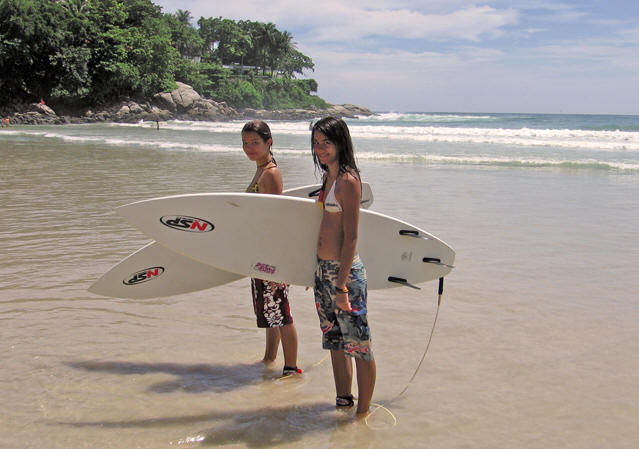 Young girls surfing at Kata Beach, Thailand