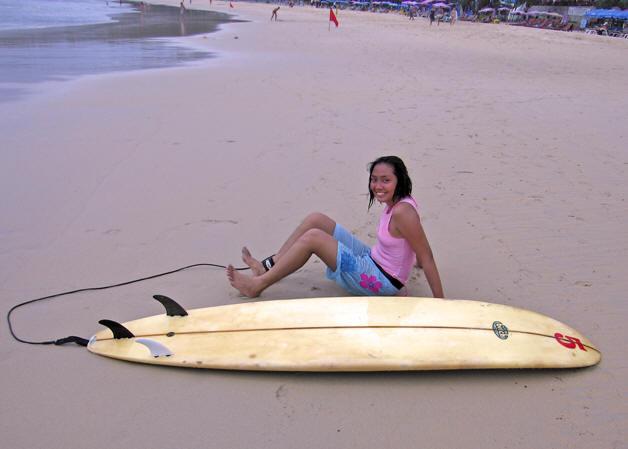 Surfer taking a rest on the beach, Kata Beach, Thailand