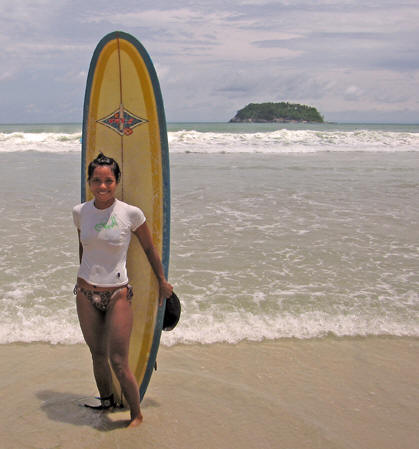 Female surfer poses with her board, Kata Beach, Thailand