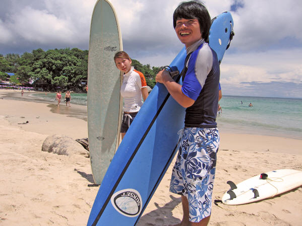 Male and female surfers getting ready to go into the sea, Kata Beach, Thailand