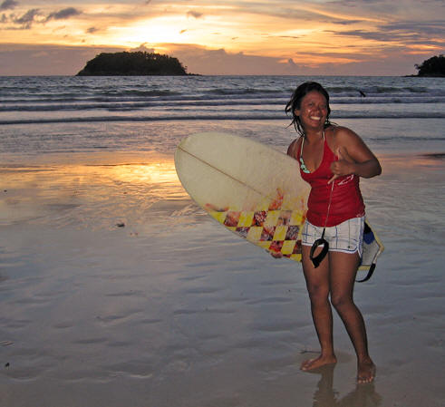 Girl surfer giving Shaka hand signal at the end of the day, Kata Beach,  Thailand