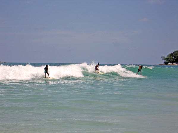 Several surfers at once on the same wave, Kata Beach,  Thailand