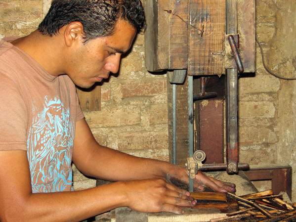 Gonza's son cutting wooden pieces from used barrels
